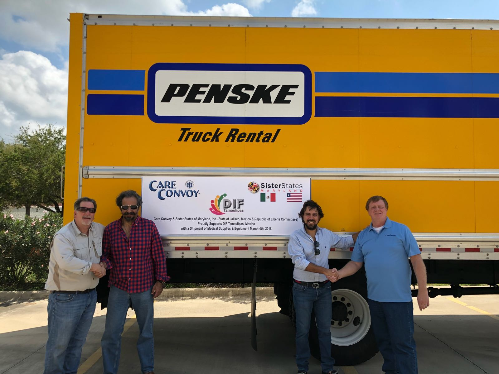 Care Convoy and Maryland Sister State representatives pose in front of their sign and a rental truck with a shipment of medical supplies to Tamaulipas, Mexico